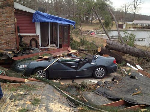 car destroyed and trees toppled in front of a house from storm damage