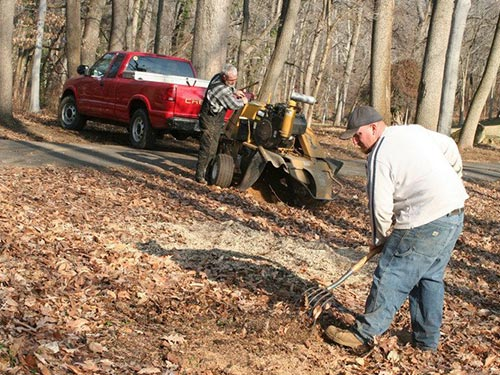 a man in a white shirt raking while another man in overalls prepping a piece of tree removal equipment behind a red pickup truck surrounded by trees